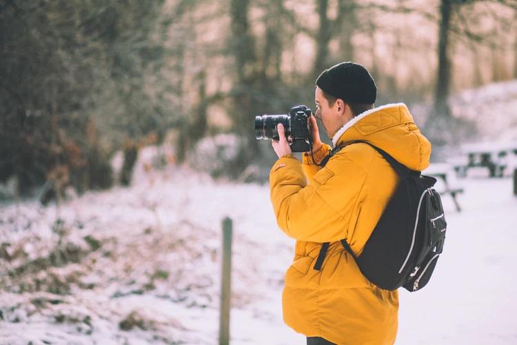 Парень в желтой куртке с фотоаппаратом в лесу